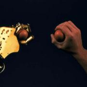 Una mano umana e una bionica stringono una pallina